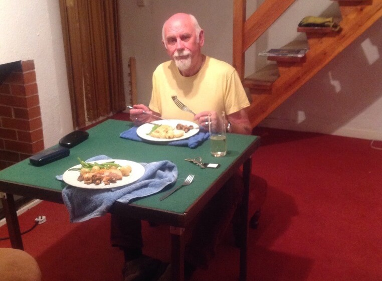 Indoor camping, eating from a card table while sitting on a foot stool from Bakewell market.